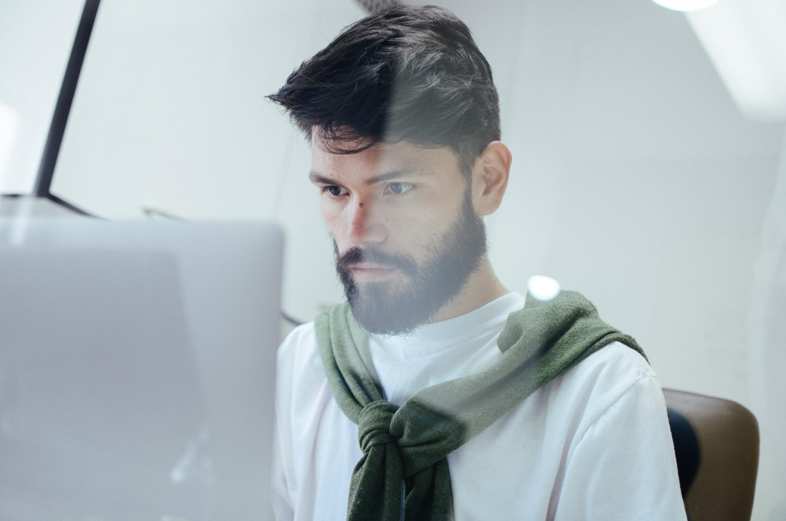 Hombre joven con barba sentado frente a un computador